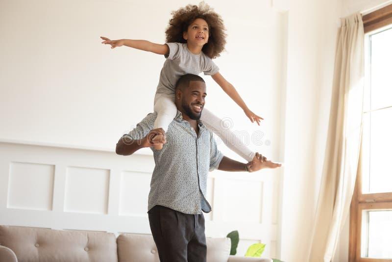 Papà nero di amore che dà piccolo giro di a due vie della figlia a casa fotografie stock