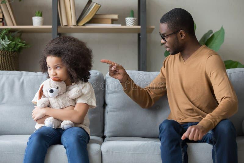 Papá africano que regaña para la hija obstinada de la disciplina que se sienta en el sofá foto de archivo libre de regalías