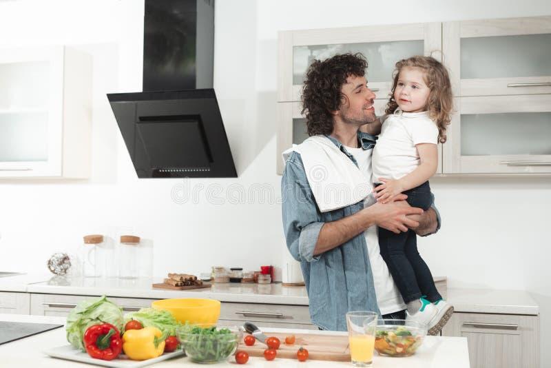 Papá alegre que detiene a la niña en cocina imagen de archivo