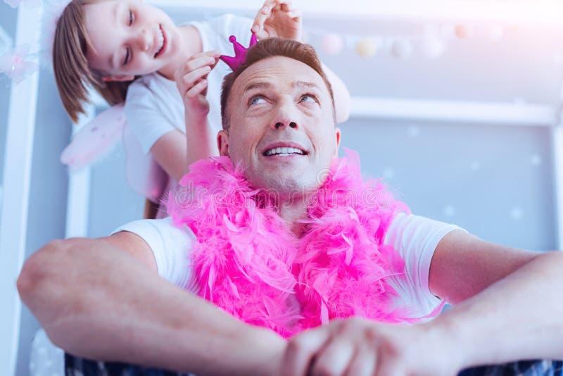 Papá atento que mira a la hija que ajusta la corona en su cabeza fotografía de archivo libre de regalías