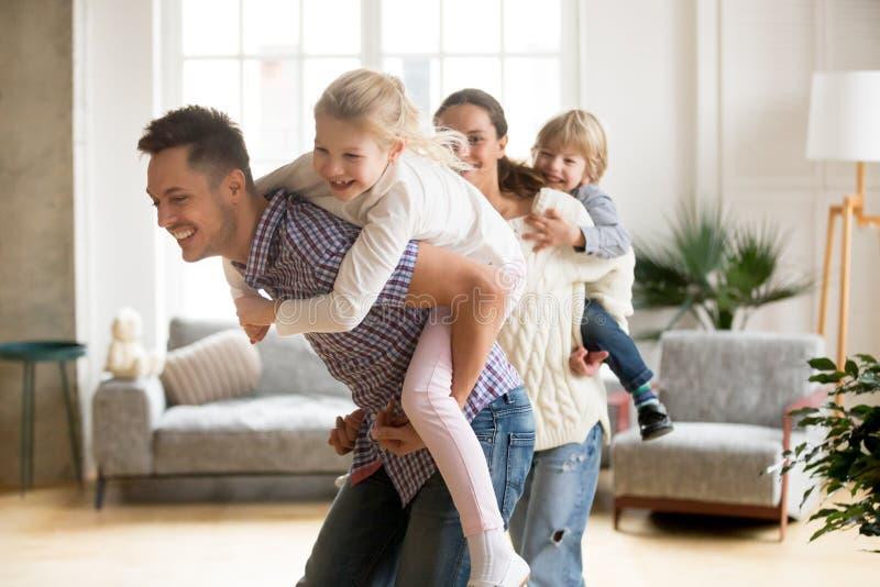 Papá cariñoso que lleva a cuestas a la pequeña hija que juega con la familia en h fotos de archivo libres de regalías