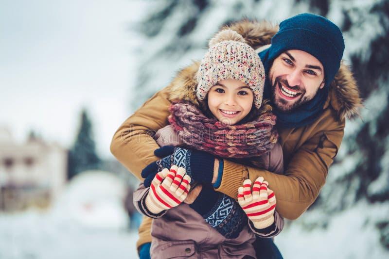 Papá con la hija al aire libre en invierno imagenes de archivo