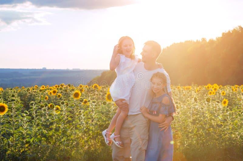 Papá con las pequeñas hijas en campo del girasol fotos de archivo