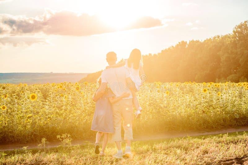 Papá con las pequeñas hijas en campo del girasol Visión trasera imágenes de archivo libres de regalías