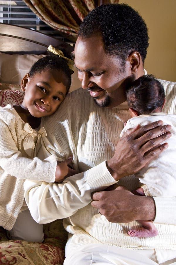 Papá con recién nacido e hija fotos de archivo
