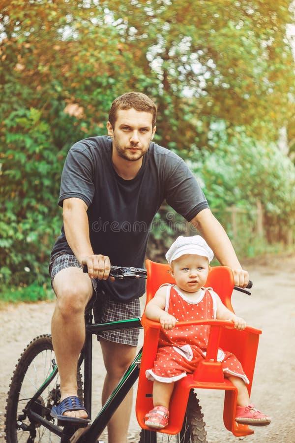 Papá con su hija en una bici fotografía de archivo