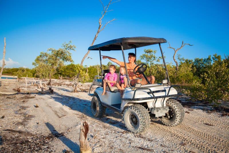 Papá con sus dos hijas que conducen el carro de golf en fotografía de archivo libre de regalías