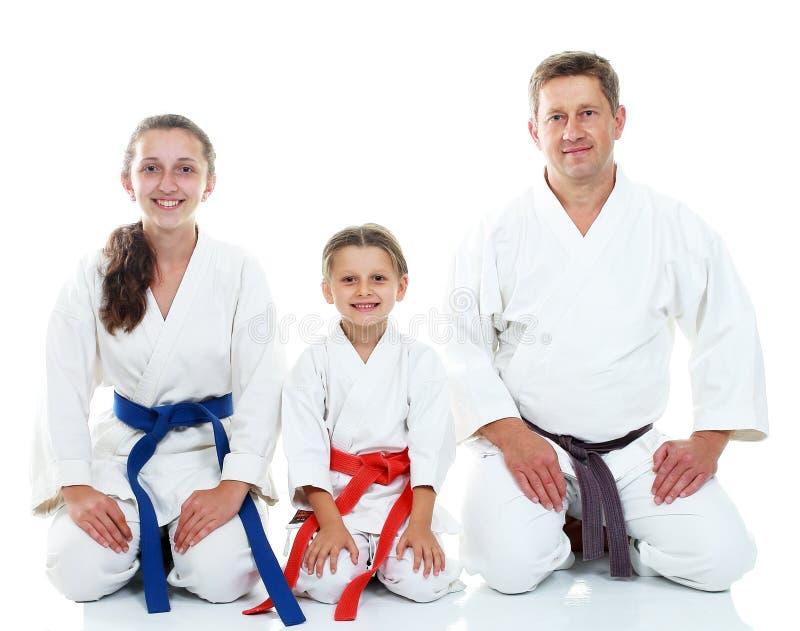 Papá con sus hijas en el kimono que se sienta en un karate ritual de la actitud imágenes de archivo libres de regalías
