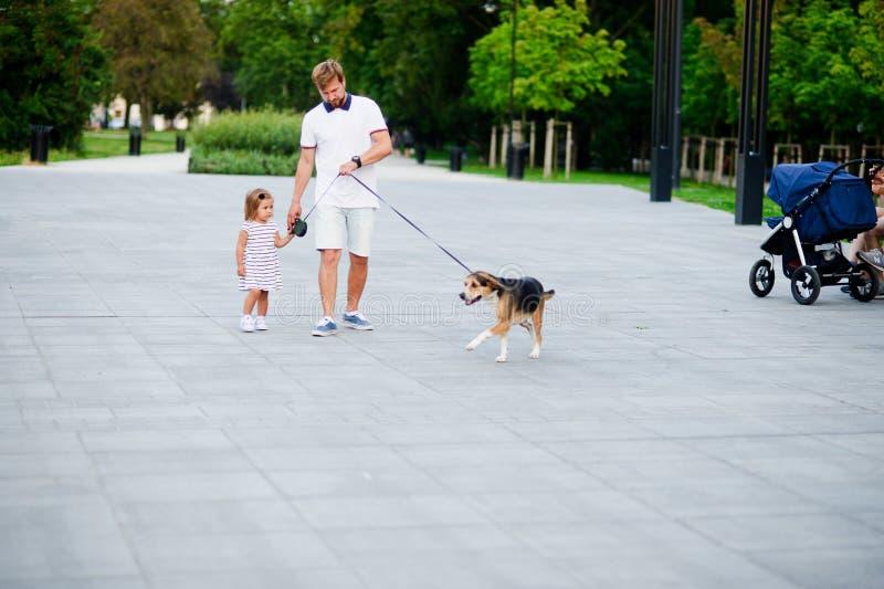Papá con una pequeña hija que camina un perro en el parque imágenes de archivo libres de regalías