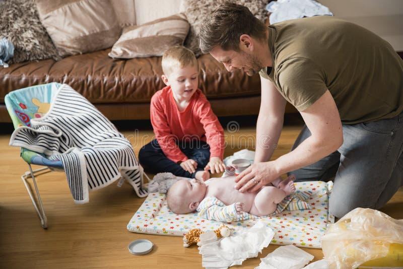 Papá de ayuda cambiar al bebé fotografía de archivo libre de regalías