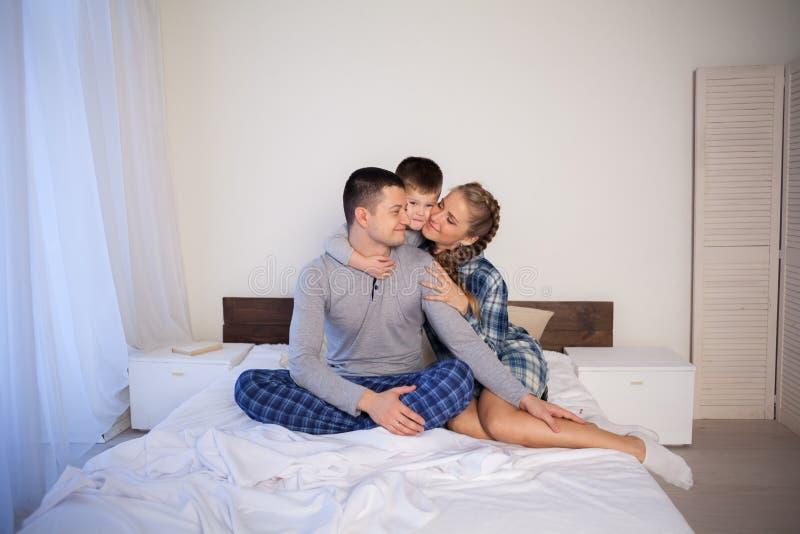 Papá de la mamá e hijo joven por la mañana en cama jugar a una familia de risa fotos de archivo libres de regalías