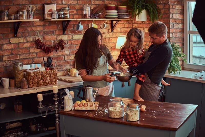 Papá de la mamá y pequeña hija junto que cocinan el desayuno en cocina del estilo del desván imagenes de archivo