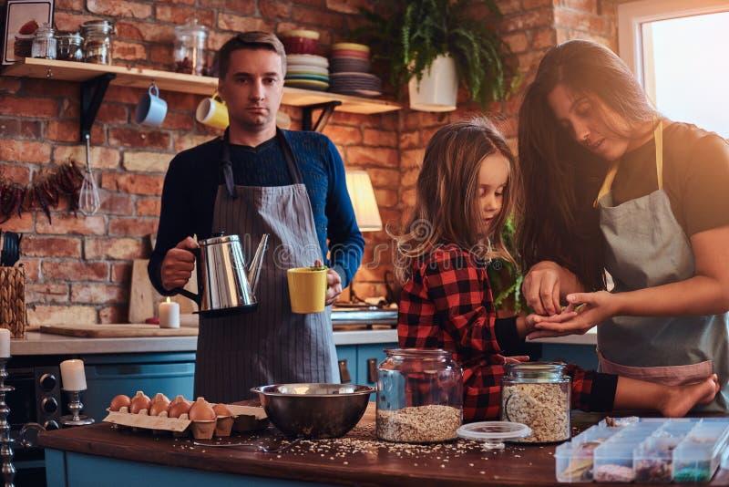 Papá de la mamá y pequeña hija junto que cocinan el desayuno en cocina del estilo del desván imagen de archivo