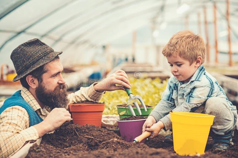 Papá de la vista lateral que mira a su muchacho precioso que juega con el suelo Inconformista con la barba elegante en el sombrer imagen de archivo