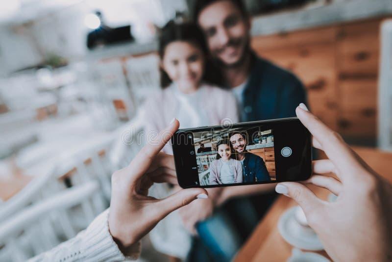 Papá de las fotografías de la madre con la hija en el teléfono móvil fotografía de archivo