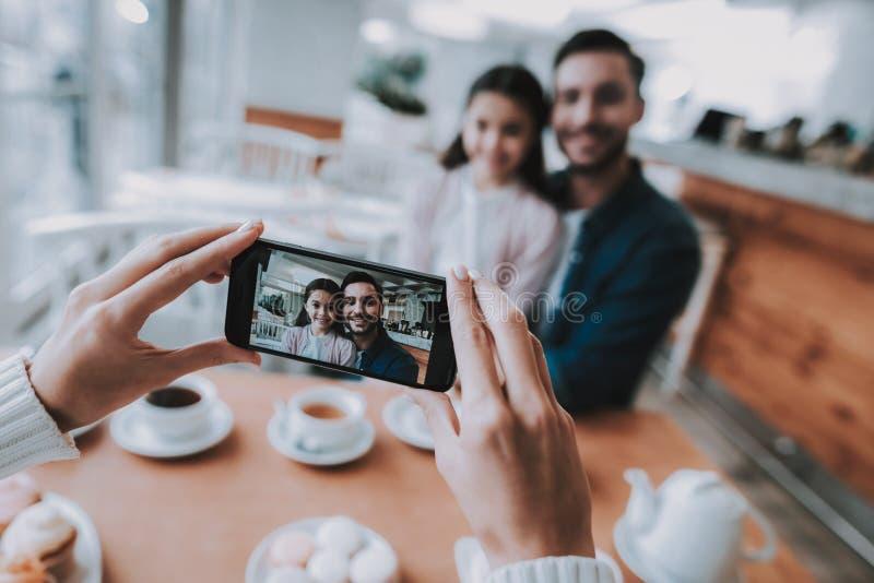 Papá de las fotografías de la madre con la hija en el teléfono móvil foto de archivo libre de regalías