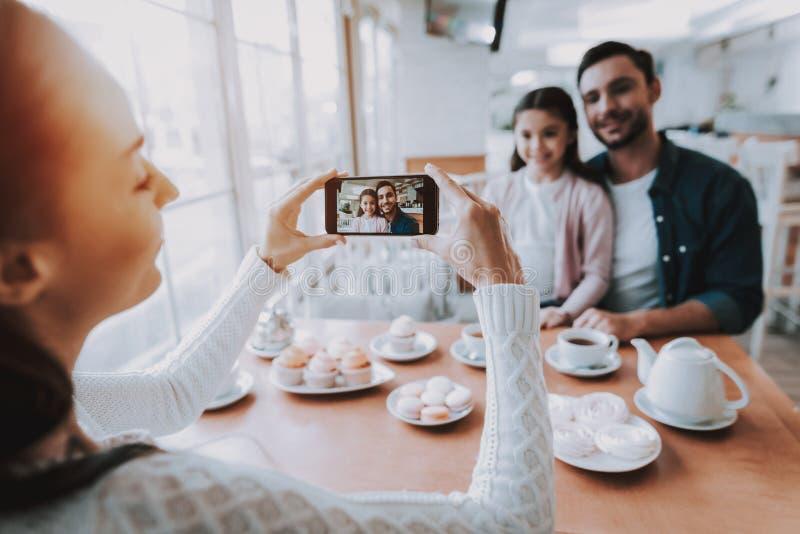 Papá de las fotografías de la madre con la hija en el teléfono móvil imágenes de archivo libres de regalías
