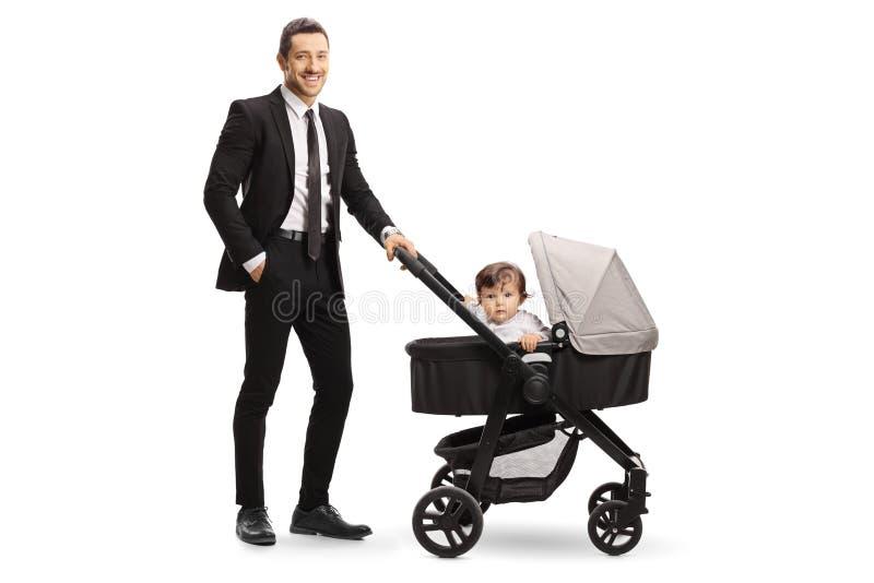 Papá de trabajo en un traje con un bebé en un cochecito fotografía de archivo