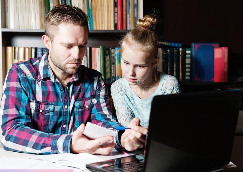 Papá e hija que aprenden junto en un ordenador portátil imagen de archivo
