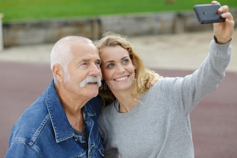 Papá e hija que hacen el retrato del selfie en el parque fotos de archivo libres de regalías