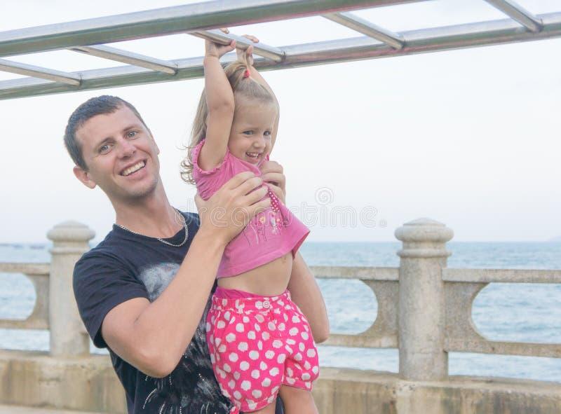 Papá e hija que juegan la 'promenade' por el mar hombre joven, ejecución de la niña en la barra fotos de archivo