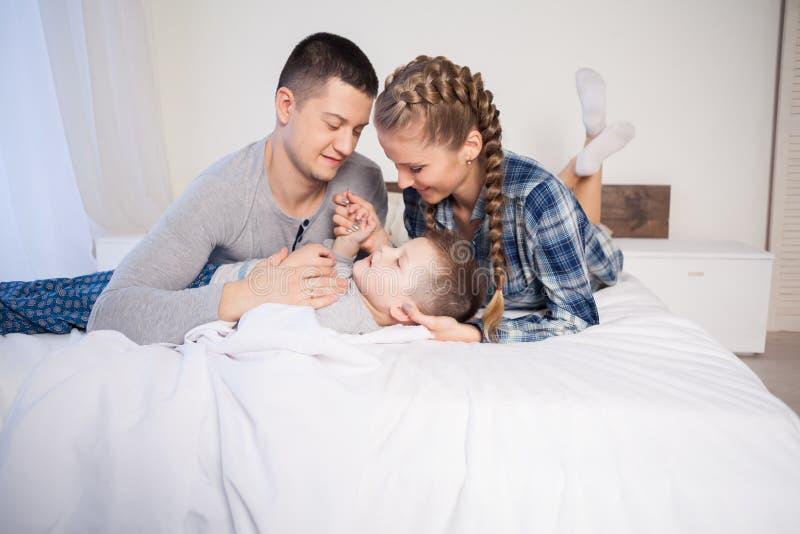 Papá e hijo de la mamá por la mañana que miente en la cama en casa en un buen humor foto de archivo
