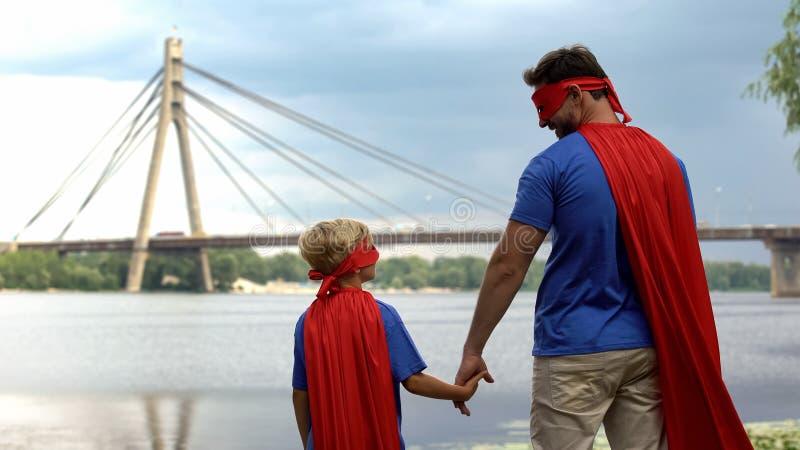Papá e hijo en los trajes del super héroe que llevan a cabo las manos, la protección del padre y la ayuda foto de archivo