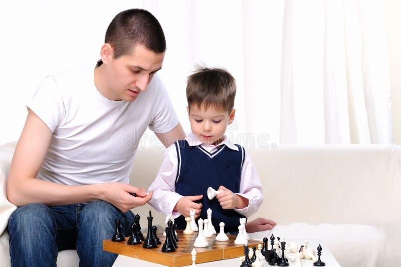 Papá e hijo que juegan a ajedrez fotografía de archivo