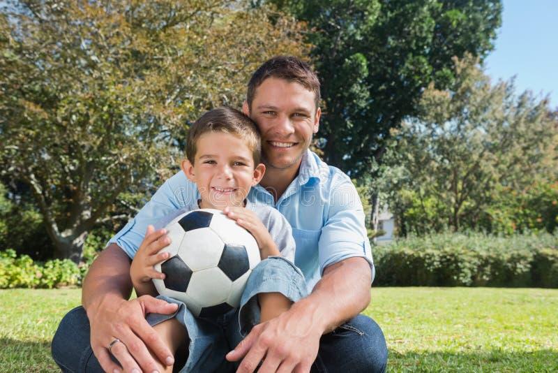 Papá e hijo sonrientes en un parque imagenes de archivo