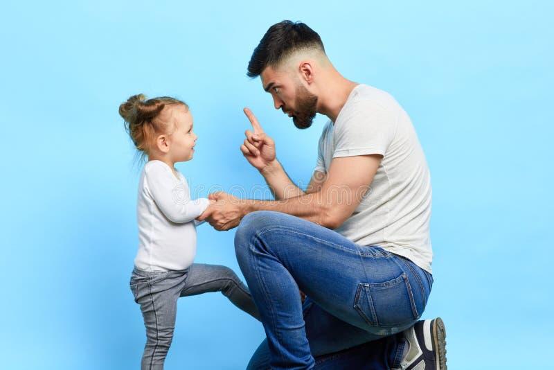 Papá estricto enojado que regaña a su poca hija traviesa del stubbon fotografía de archivo