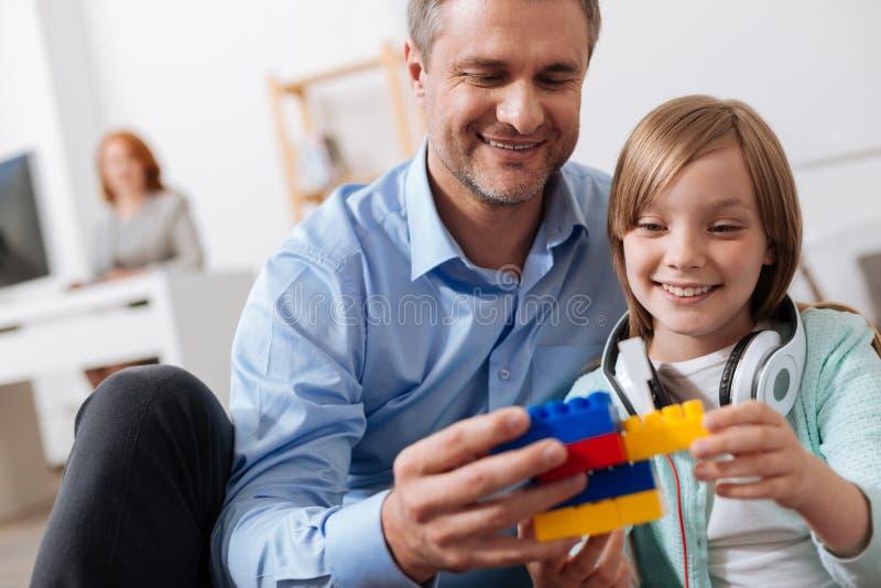 Papá feliz carismático que disfruta de la compañía de los niños en el trabajo fotos de archivo libres de regalías