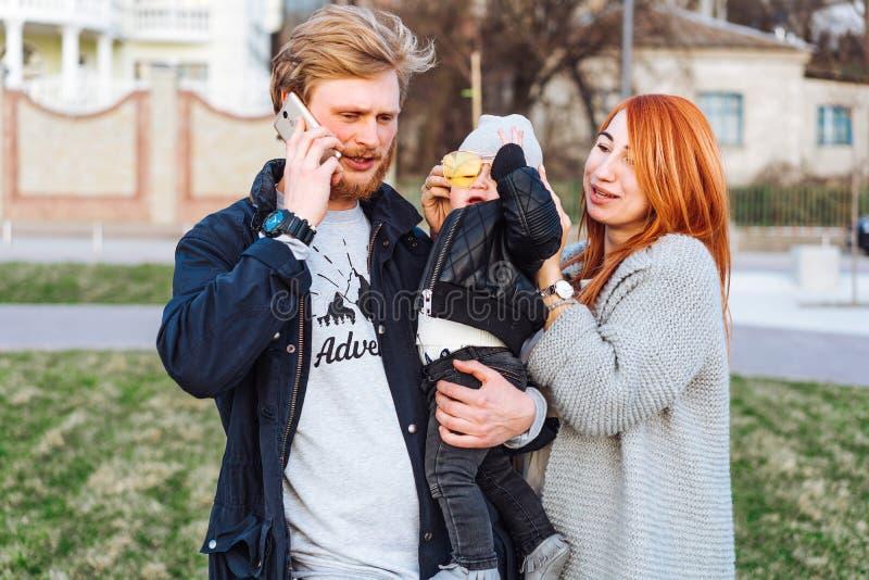 Papá feliz e hijo de la mamá que abrazan en el parque imagen de archivo libre de regalías