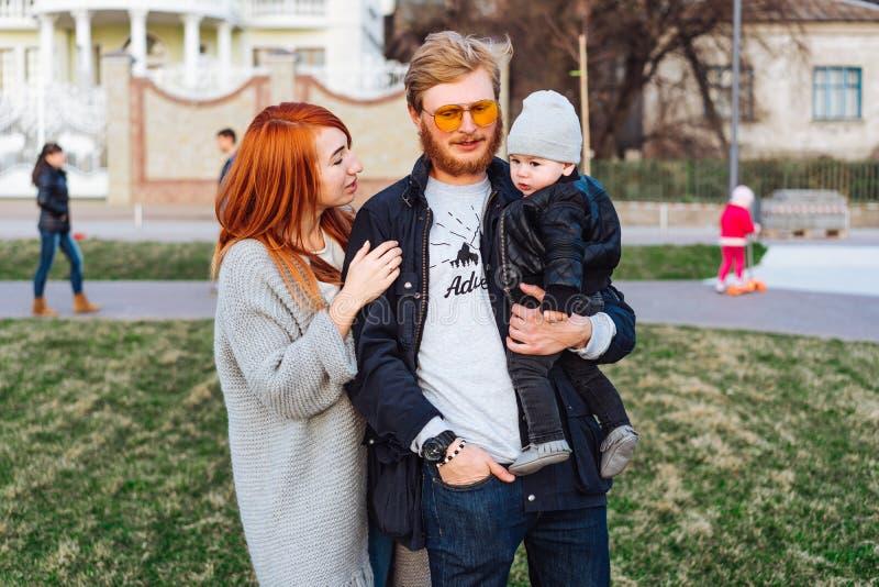 Papá feliz e hijo de la mamá que abrazan en el parque foto de archivo