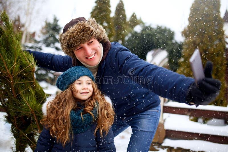Papá hermoso e hija que hacen el selfie con el árbol de navidad recientemente cortado con smartphone cerca de hogar Familia joven foto de archivo libre de regalías