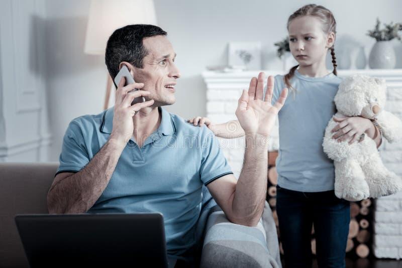 Papá indiferente que habla en el teléfono móvil foto de archivo