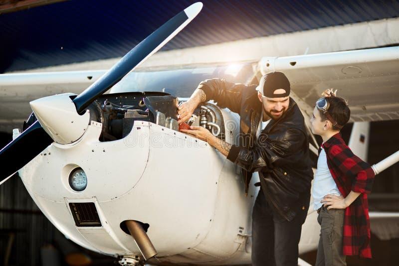 Papá joven e hijo que hablan del primer vuelo inminente, reparando el motor plano imágenes de archivo libres de regalías