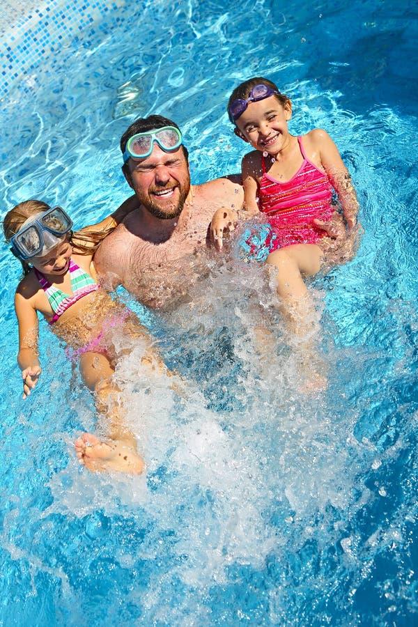 Papá joven y pequeña hija que extienden en la piscina que disfruta de vacaciones de verano foto de archivo libre de regalías