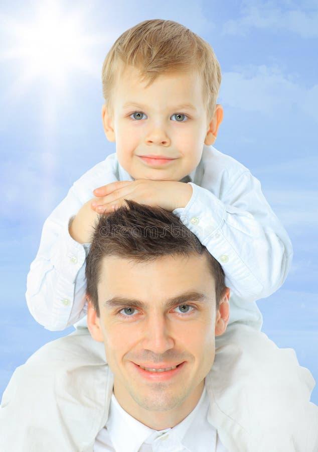 papá lindo del papá de los brazos del bebé de la playa del muchacho azul de la nube caucásica hermosa adorable del niño imagen de archivo libre de regalías