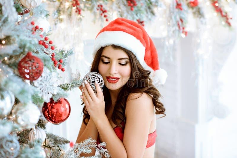 Papá Noel atractivo moreno hermoso en sombrero y sujetador elegantes imágenes de archivo libres de regalías
