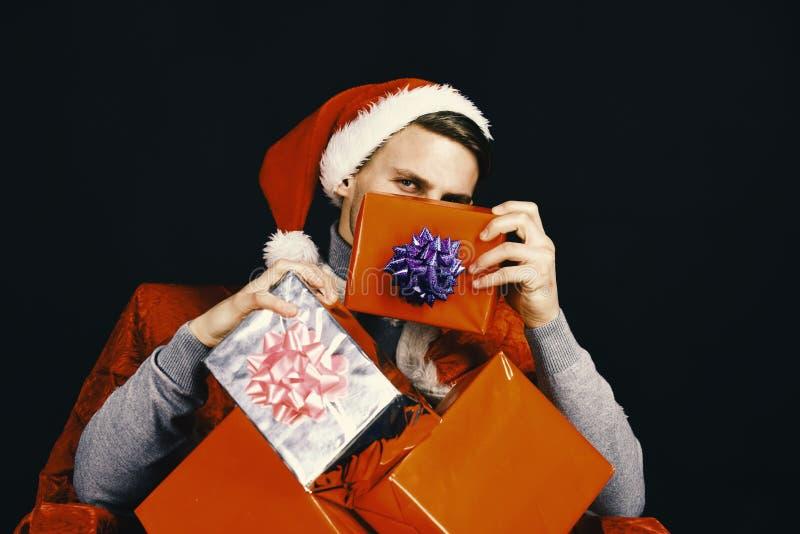Papá Noel con los presentes en fondo negro Individuo con la cara tímida imagenes de archivo