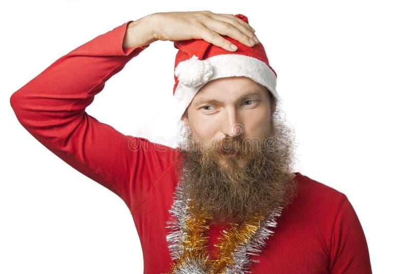 Papá Noel divertido infeliz con la barba real y sombrero y camisa rojos que miran la cámara con tristeza Aislado en blanco fotografía de archivo libre de regalías