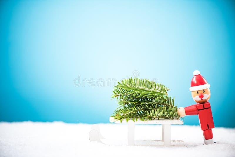 Papá Noel divertido lleva el árbol de navidad en nieve imágenes de archivo libres de regalías
