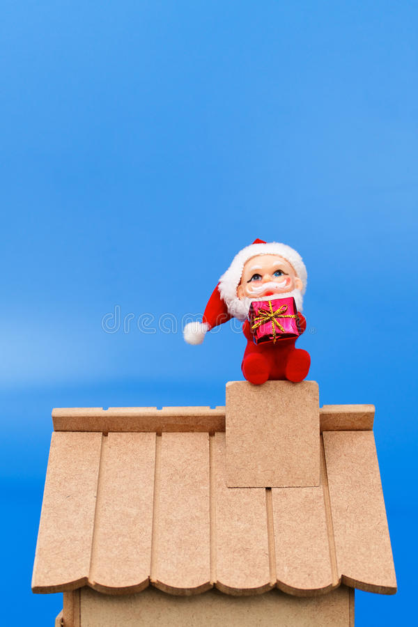 Papá Noel en la azotea que sostiene un regalo fotografía de archivo libre de regalías