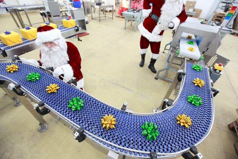 Papá Noel en la cadena de producción del ornamento de la Navidad imagenes de archivo