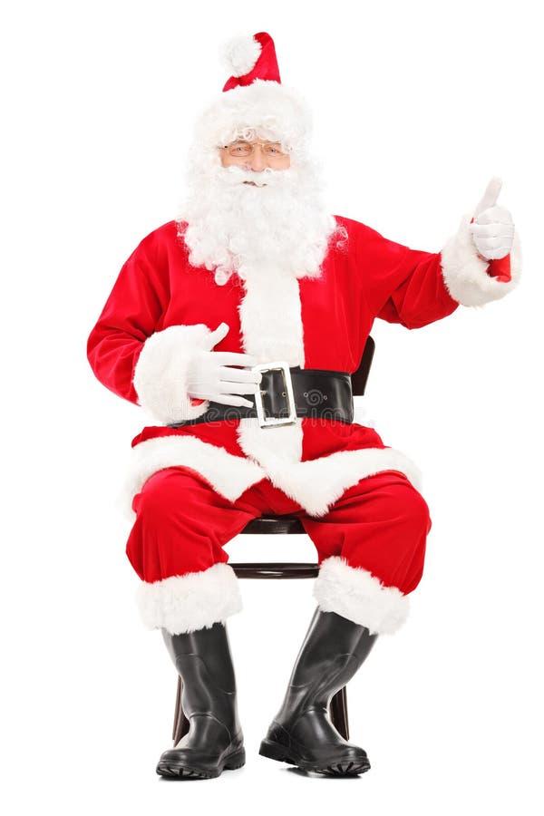 Papá Noel feliz que se sienta en una silla de madera y que da un pulgar u imágenes de archivo libres de regalías