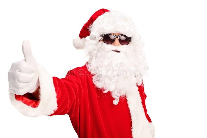 Papá Noel fresco con las gafas de sol que dan un pulgar para arriba fotografía de archivo libre de regalías