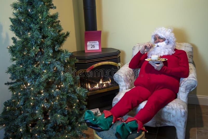 Papá Noel que come las galletas después de la Navidad imágenes de archivo libres de regalías
