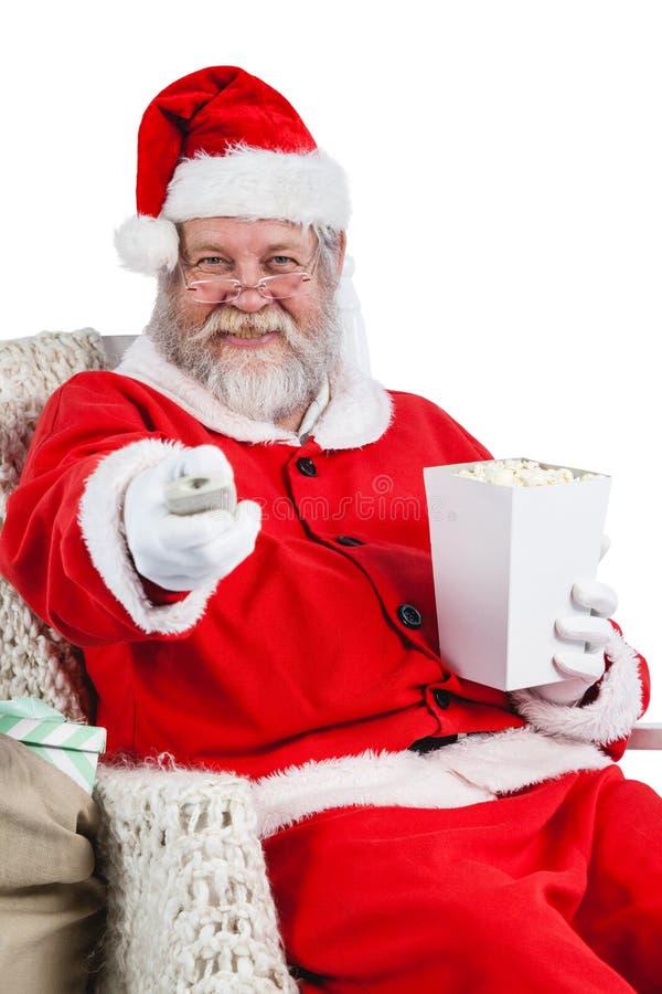 Papá Noel que come palomitas mientras que ve la TV foto de archivo libre de regalías