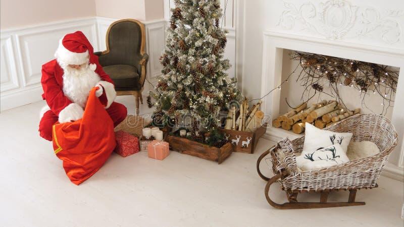 Papá Noel que entrega presentes debajo del árbol de navidad imagen de archivo