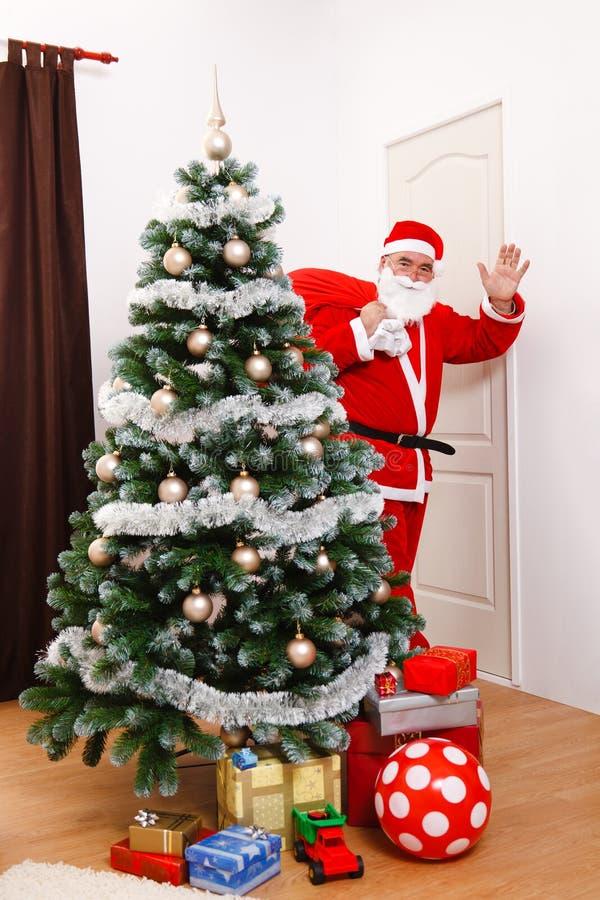 Papá Noel que mira detrás y que saluda imagen de archivo libre de regalías